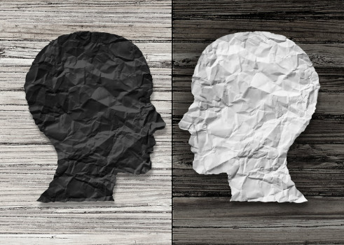 Bipolar mental health and brain disorder concept as a human head in paper divided in two colors as a neurological mood and emotion symbol or medical psychological metaphor for social behavior challenges in a 3D illustration style.